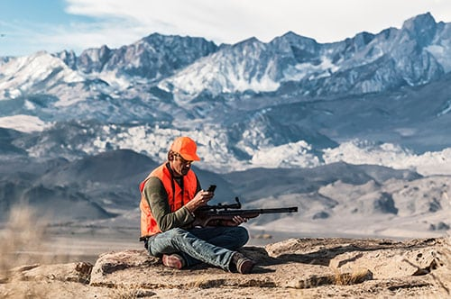 Hunter reading sms marketing while hunting on a mountain.